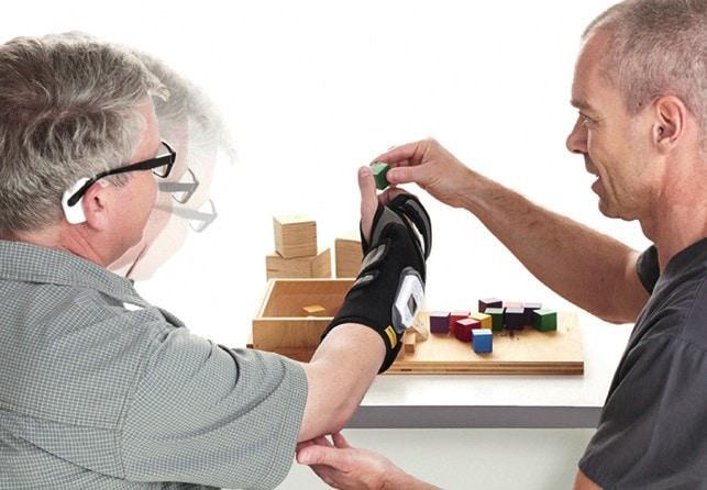 """Funktionelle Elektrostimulation mit der Unterarmorthese """"ReGrasp"""". Die Ansteuerung der Hand erfolgt über einen Sensor, der hinter dem Ohr getragen wird und auf Bewegungen des Kopfes reagiert."""