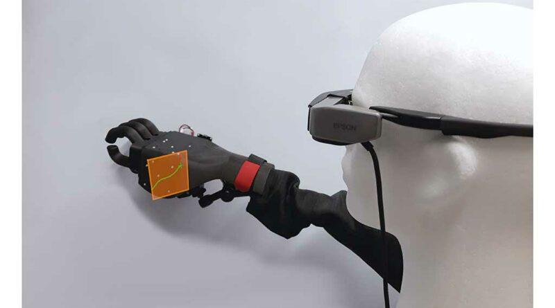 Darstellung der visuellen Steuerung einer Handprothese. Das eingeblendete orangene Rechteck ist das virtuelle Kommandofeld, das nur vom Nutzer (durch die AR-Brille) gesehen wird. Der grüne Cursor sowie die Leuchtspur visualisieren dem Nutzer, auf welche Stelle er gerade blickt. Oben auf der Prothese sind die LED-Tripletts zu sehen.