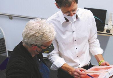 Filialleiter und Orthopädietechniker-Meister Matthias Roßmann erläutert MdB Maria Klein-Schmeink kritische Stellen ihres Fußabdrucks beim Besuch der Grünen-Politikerin Sanitätshaus Micke & Co, bei dem auch die Online-Einlagenversorgung ein Thema war.